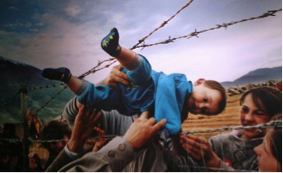child being lifted by adults through a fence